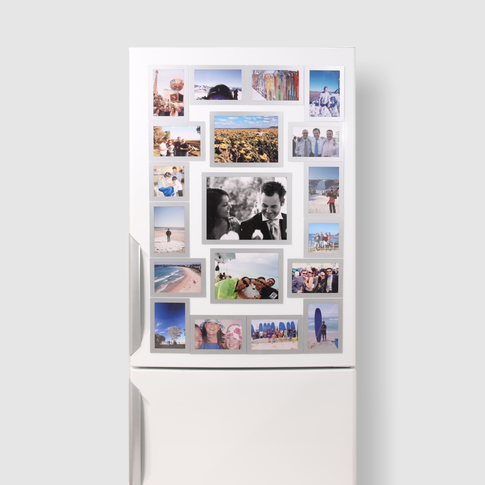 A collection of big silver Magnetic Picture Frames on a white Refrigerator